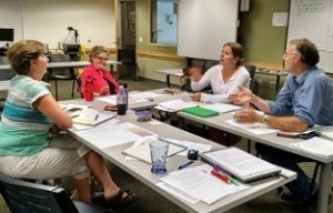 four people talking around a meeting table